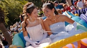 Two girls wearing quinceanera dresses riding an attraction