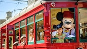 Conductor Mickey and a girl smile from the helm of a Red Car Trolley