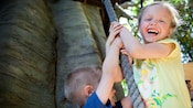 Two kids laugh as they pull down on a rope at Tarzan's Treehouse