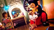 A girl gets a hug from a famous Mouse at Mickey's House and Meet Mickey attraction