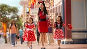 A mother and her 2 daughters stroll down Main Street, U.S.A., happy to receive Passholder discounts