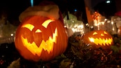 Glowing and grimacing Jack-o'-lanterns with jagged teeth