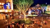A dramatically lit evening view of a Downtown Disney District plaza with Guests enjoying music