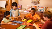 Four children enjoy a board game in an activity center stocked with family games