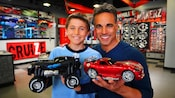 A father and son proudly hold up the tricked-out toy cars they made at RIDEMAKERZ