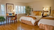 A room with a hardwood floor, 2 queen beds with headboards, a desk and windows with shutters
