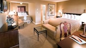 A suite with a queen bed, love seat, coffee table, desk, easy chair, dresser and daybed