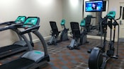 A hotel fitness room includes a variety of exercise machines and a flat-screen TV