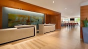 The front desk of the Wyndham Hotel features contrasting wood and modern art with a view of the wine bar