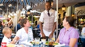 Diners under a shady umbrella enjoy friendly service at the outdoor Café Orleans restaurant