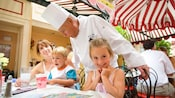 A Carnation Cafe chef visits a mother and 2 children as they dine at this outdoor Disneyland restaurant