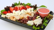 A salad with turkey breast, strawberries, feta cheese, cranberries, nuts and jicama with mixed greens