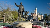 Partners statue of Walt Disney holding hands with Mickey Mouse and, beyond, Sleeping Beauty Castle