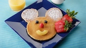 A plate of Mickey pancakes with blueberry eyes, strawberry nose and pineapple smile