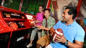 Guys test their football tossing skills at ESPN Zone Sports Arena and arcade