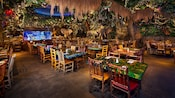 Dining tables and chairs under the lush Rainforest Cafe jungle