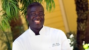 Chef Alle Thiam, dressed in his white chef jacket, smiles for the camera.