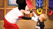 A toddler touches the tip of Mickey's nose; Mickey touches the toddler's nose