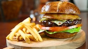A juicy cheeseburger with bacon, lettuce, tomatoes and pickles on a bun with a side of French fries