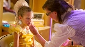 A Fairy-Godmother-in-Training completes a girl's transformation to princess with lipstick