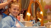 While seated in a Bibbidi Bobbidi Boutique salon chair, a girl gets her hair styled