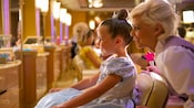 A young girl and a Fairy-Godmother-in-Training look into a salon-style mirror