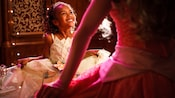A girl smiles and curtsies as she meets a Disney Princess at The Royal Hall in Fantasy Faire