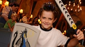 A boy brandishes a decorative sword and shield, part of the Knight Package at Bibbidi Bobbidi Boutique