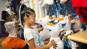 Young female Guests peruse Olaf plush dolls and other 'Frozen' merchandise at Anna & Elsa's Boutique