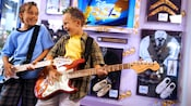 Two boys strum electric guitars inside the Studio Disney 365 shop