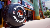 A giant tire with the sign RIDEMAKERZ at the entrance of the Downtown Disney shop