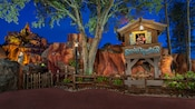A sign for Splash Mountain near the entrance to the attraction in Frontierland at night