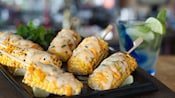 Six skewered Central American Crazy Corn on the cobs with spicy pepper sauce and melted cheese