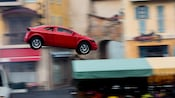 A red car flies through the air at Lights, Motors, Action! Extreme Stunt Show