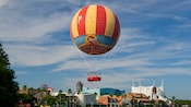 A helium balloon covered with classic flying Disney characters hovers over Downtown Disney area