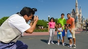 A Disney PhotoPass Photographer snaps a picture of a family standing in front of Cinderella Castle