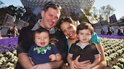 A mother and father hold their 2 young boys while sitting in front of Spaceship Earth in Epcot