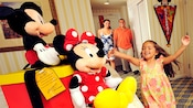 A young girl runs toward Mickey and Minnie Mouse plush while her parents look on excitedly in the doorway