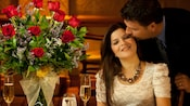 A romantic dinner featuring a vase of roses on top of a table where a happy couple is sharing a warm embrace