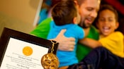 An award for best dad and a Mickey Mouse medal sit in the foreground as a dad hugs his sons in the background