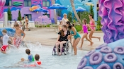 A young female Guest in a wheelchair enjoys some poolside fun at Disney's Art of Animation Resort