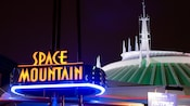 The lighted exterior sign for Space Mountain and the attraction after dark