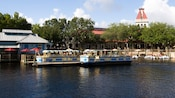 2 ferry boats adorned in blue, yellow and white wait at the dock for park Guests