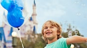 A smiling boy holds a Mickey Mouse balloon with Cinderella Castle in the background