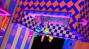 An upside-down bathtub with geometric patterns and Figment taking a bath