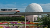 A monorail train gliding over a pond close to Spaceship Earth at Epcot