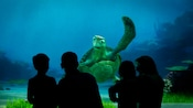 Crush waves to a family of 4 silhouetted against the screen at Turtle Talk with Crush