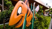 Large outdoor sculpture of an orange fish at Voyage of the Little Mermaid