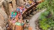 Guests riding a roller coaster shaped like a mine cart train