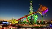 The futuristic and colorful Astro Orbiter attraction illuminated at night in Tomorrowland